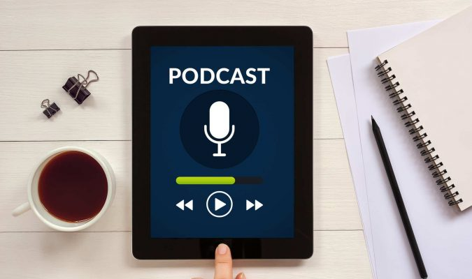 Podcast concept on tablet screen with office objects on white wooden table. All screen content is designed by me. Flat lay